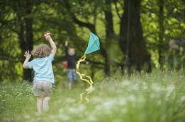 Little girl running with a kite through a forest